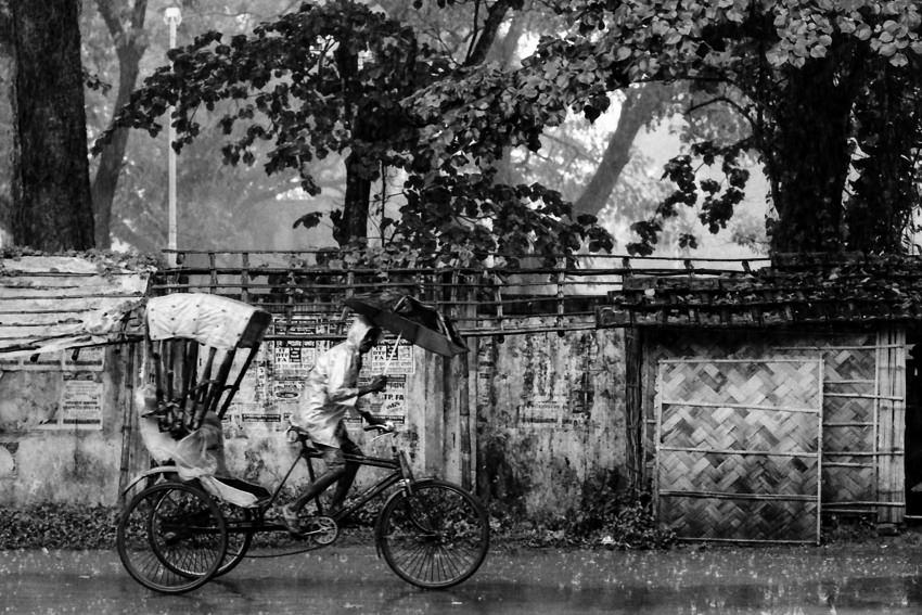 雨の中を走るサイクルリクシャー