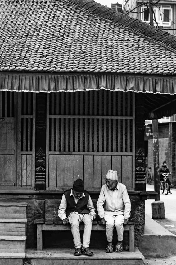 Two sitting men by wayside