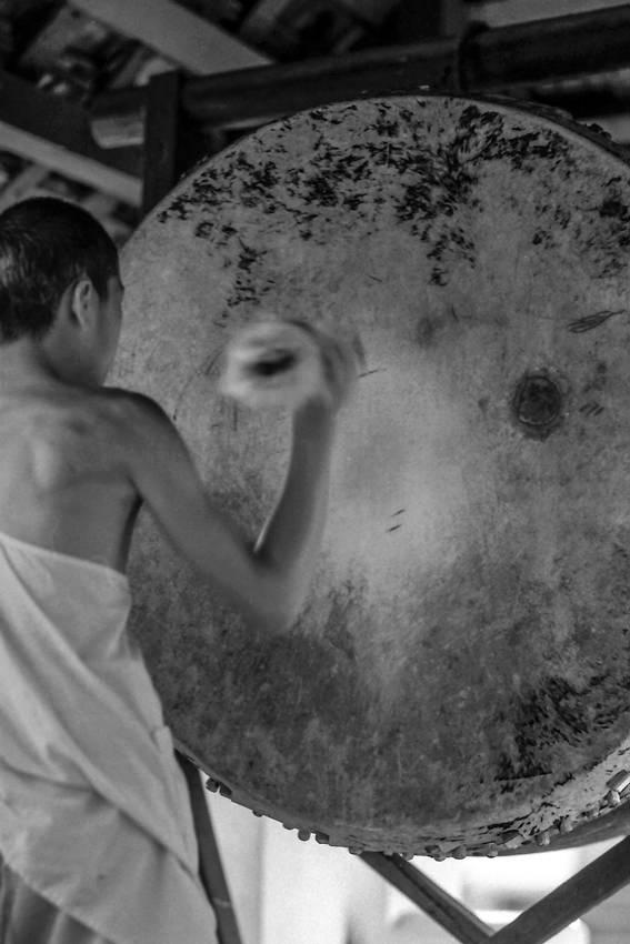Young monk drumming big drum