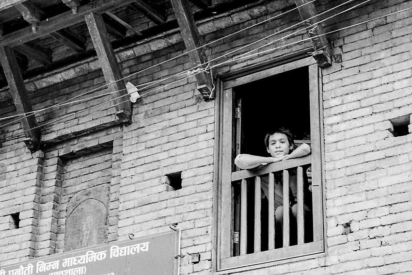 窓から外を眺める男の子