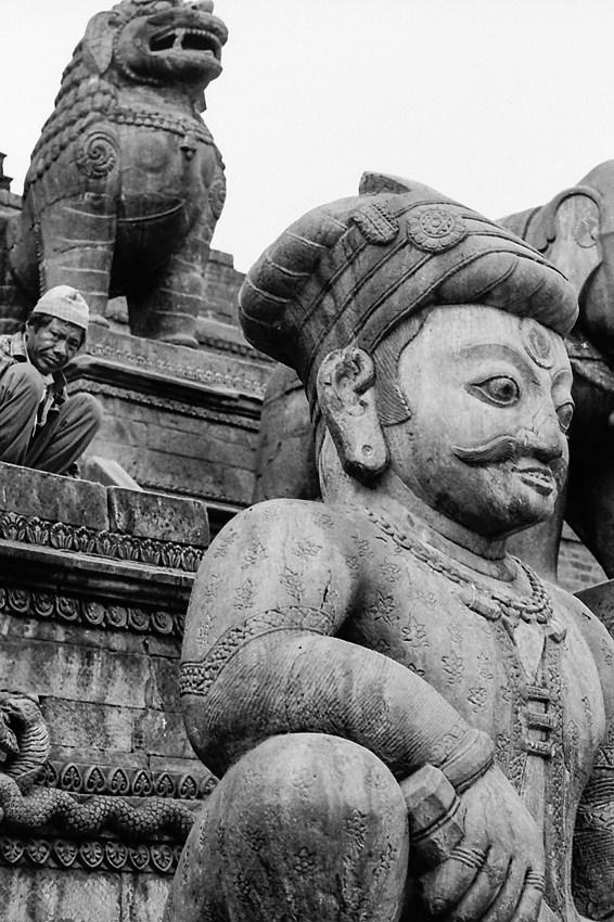 Man behind stone statue
