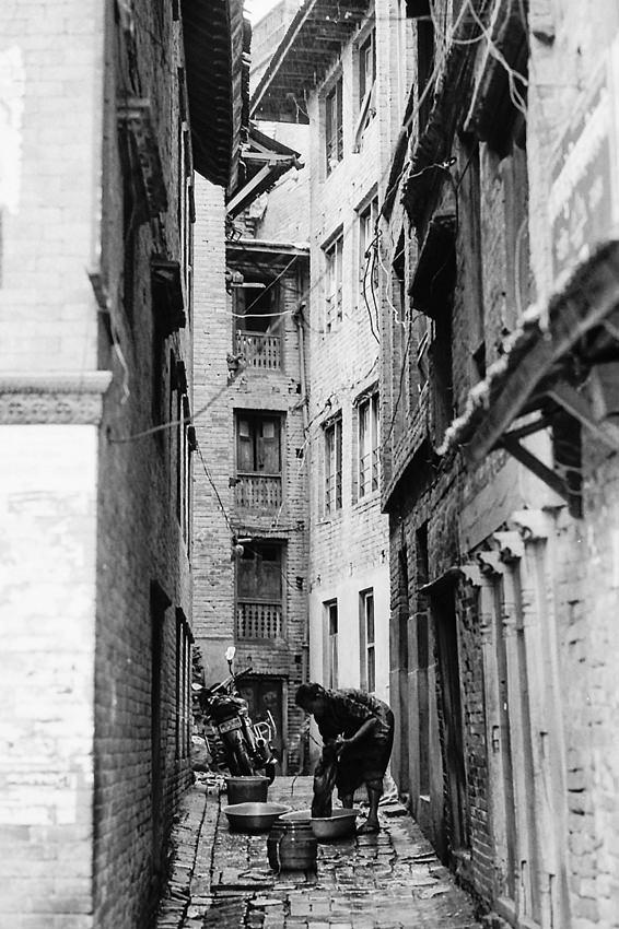 薄暗い路地で洗濯する女