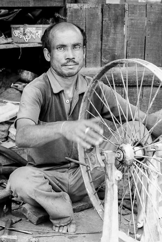 サイクルリクシャーを修理する男