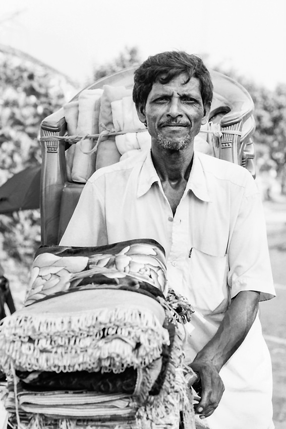 Man carrying furniture by bicycle