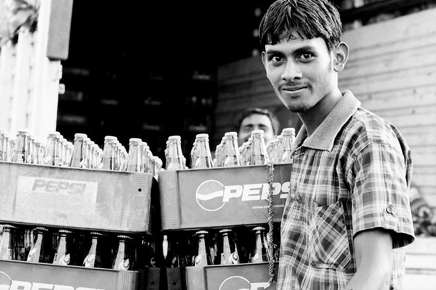 ジュースの瓶の横に立つ男