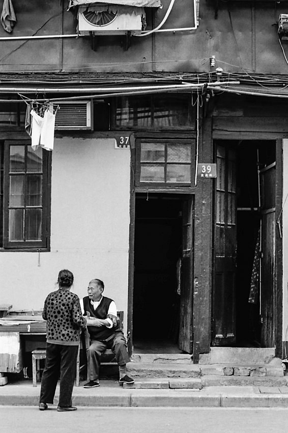 Old couple relaxing in front of house