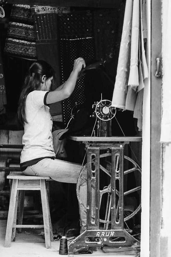 Woman sitting in front of sewing machine with a foot treadle