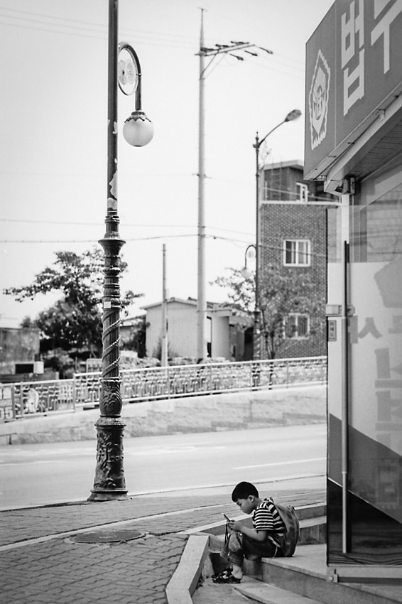 Boy playing hand-held game by the wayside