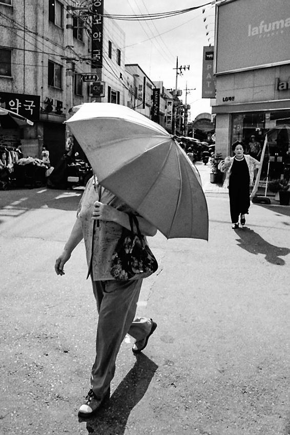 傘を差して歩く小太りの女