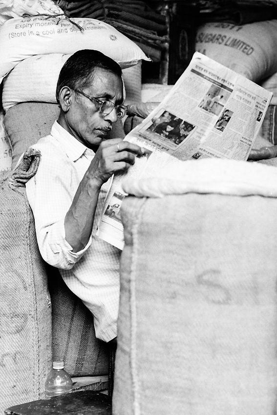 Man reading newspaper among hemp sacks