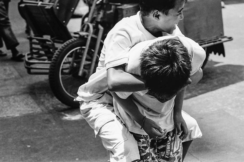 Boy holding onto boy tightly