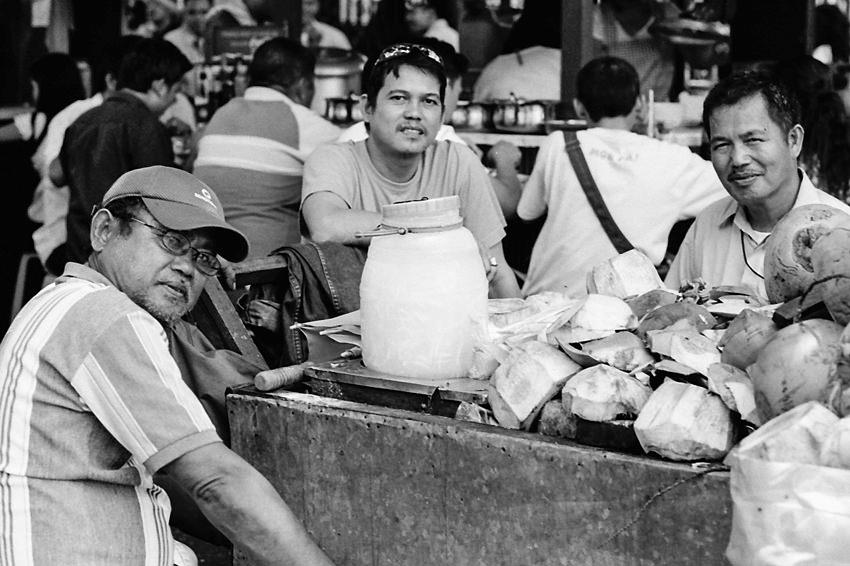 Men surrounding shells of coconut