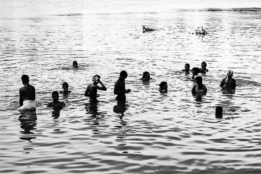 Silhouetted people soaking in Mahananda river