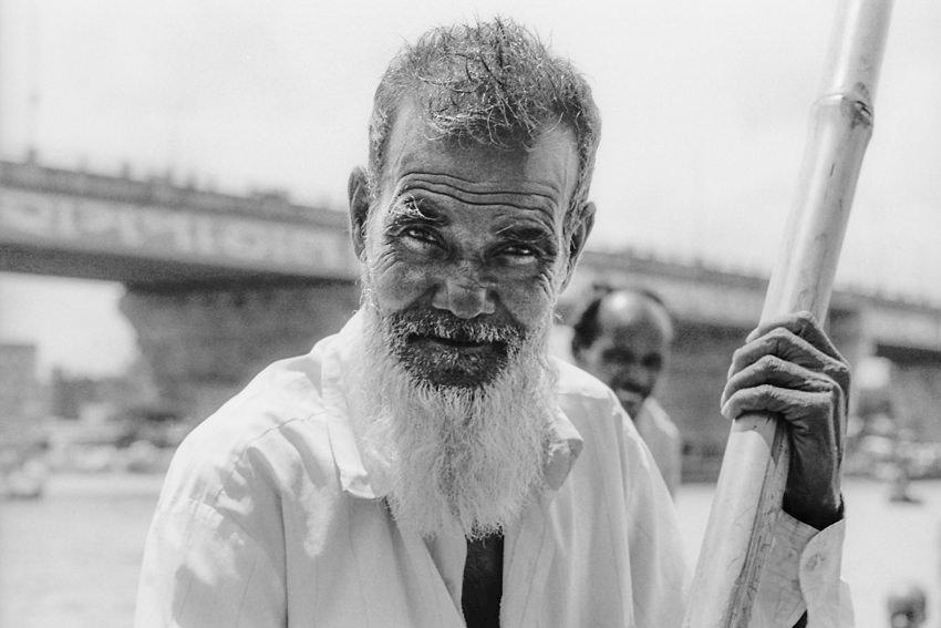 Old man holding bamboo oar