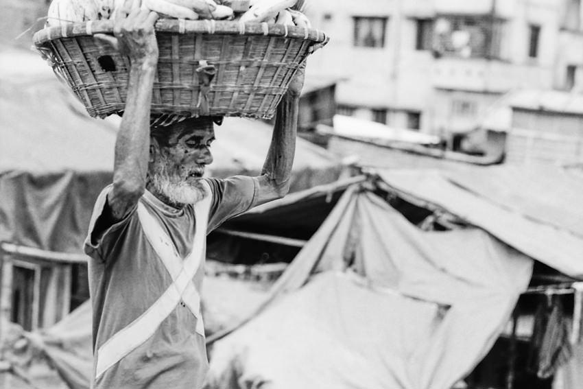 籠を運ぶ年配の労働者