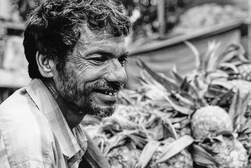 Man smiling beside pineapples