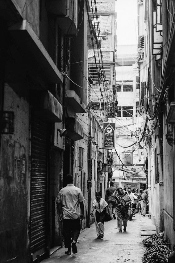 Dim alleyway between buildings in Dhaka