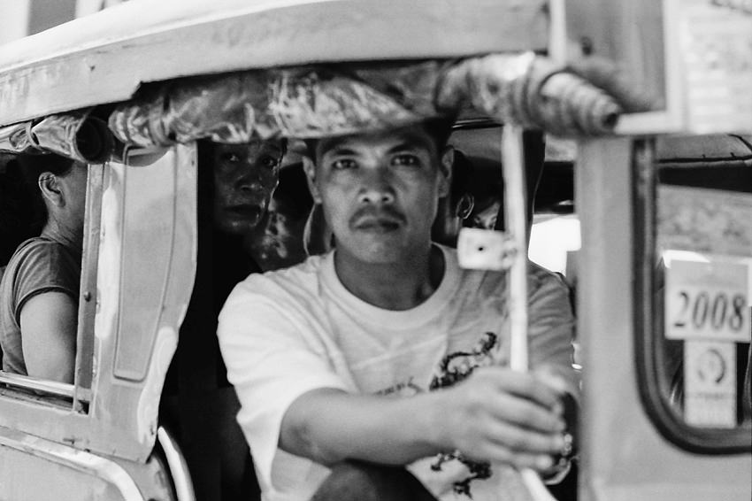 Man holding the handrail on Jeepney