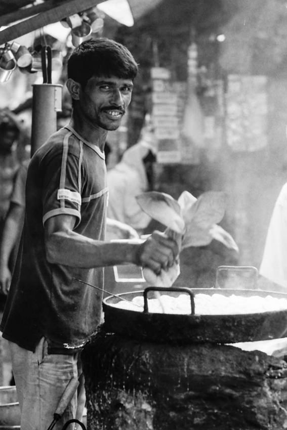 Man working in food stall with round pan