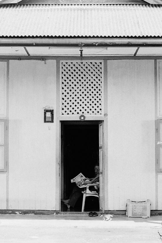 玄関で新聞を読む男