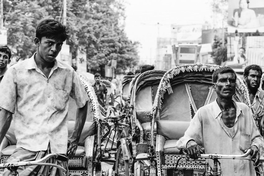 Cluster of cycle rickshaw being stopped at traffic light