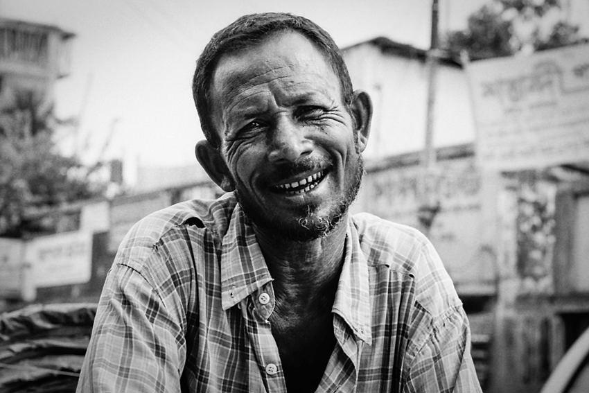 笑い皺のあるサイクルリクシャーの車夫