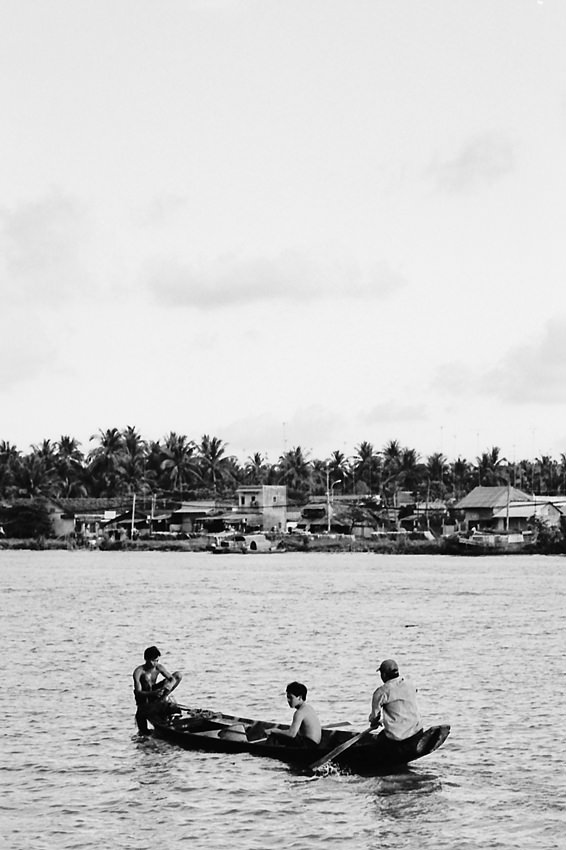 Three men on wooden boat
