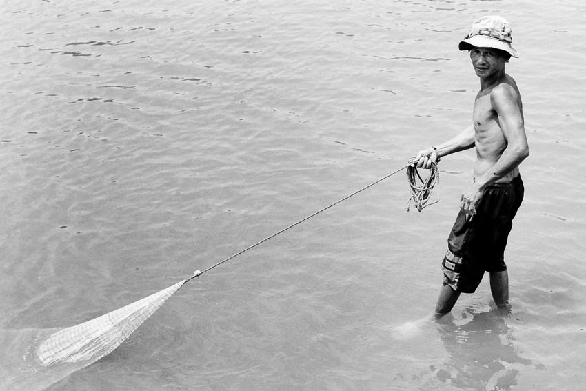 Man dragging fishnet in the river