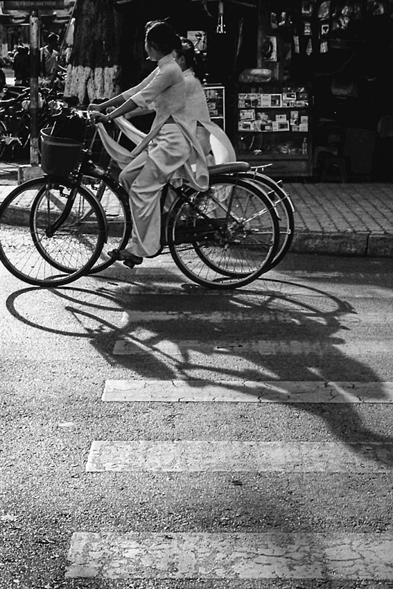 Girls wearing Ao Dai riding bicycle