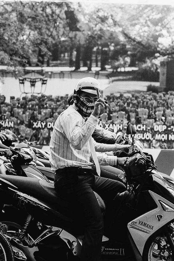 バイクの上でピースサインをする男