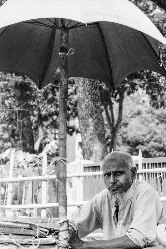 日傘の下で暇を持て余す男