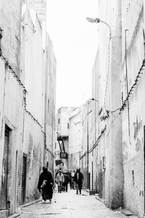 People walking alleyway without windows