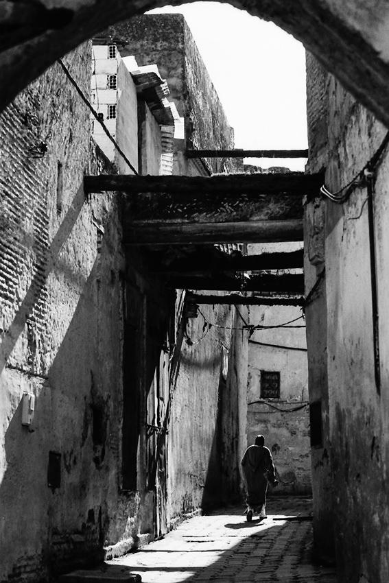 Figure walking narrow lane