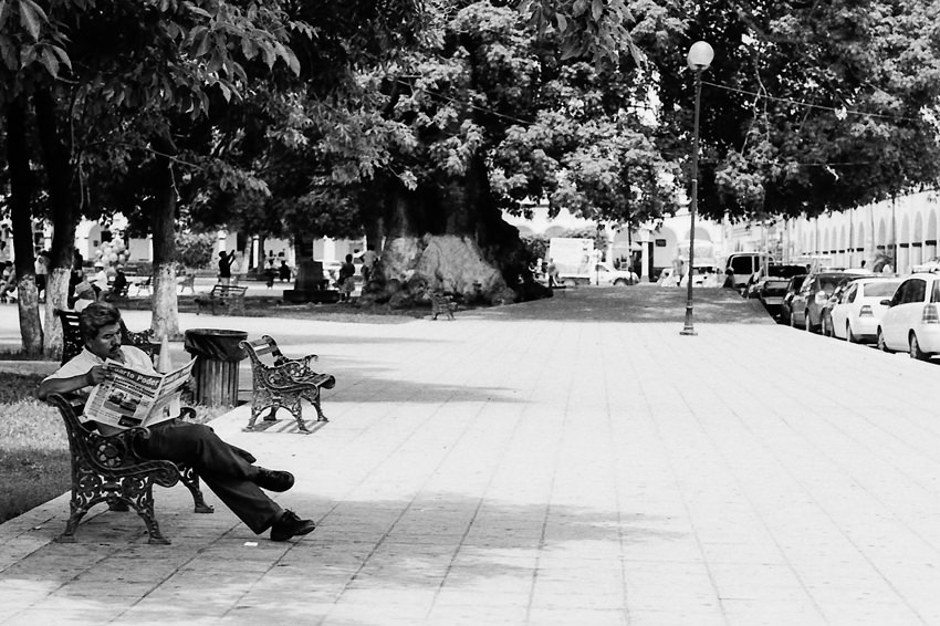 Man reading newspaper in the shade
