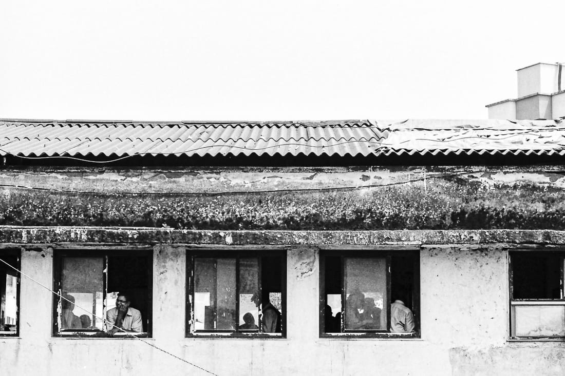 Figures by windows of zinc-roofed building