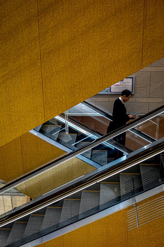 Businessman wearing a business suit on escalator