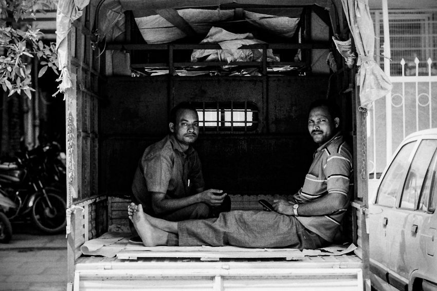 Two men sitting in luggage carrier