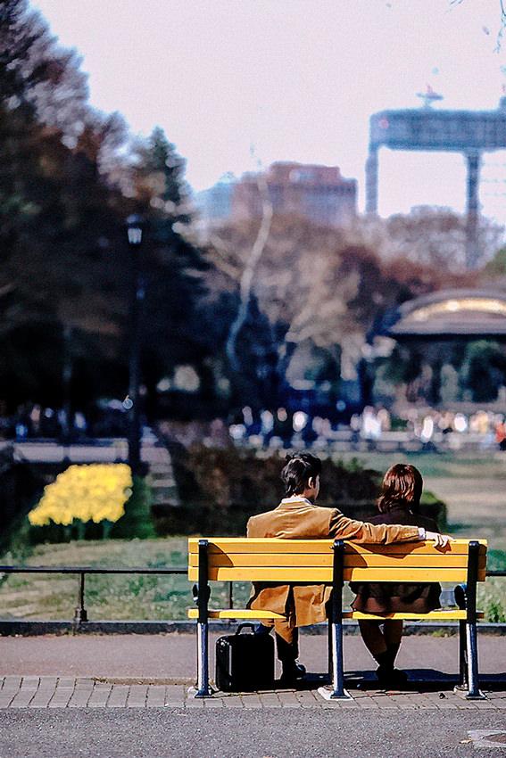 Couple sitting on bench in Hibiya Park