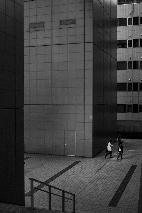 Two Figures Beside A Thick Pillar (Tokyo)