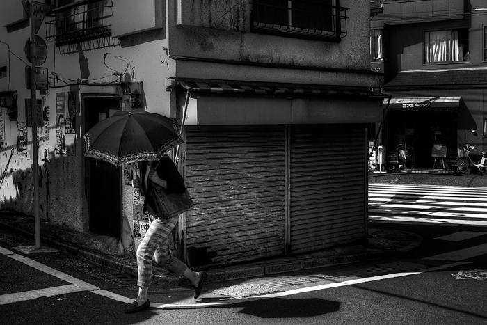 シャッターの前を通り過ぎる傘