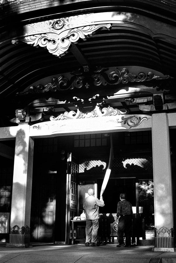 王子神社で鈴を鳴らす男