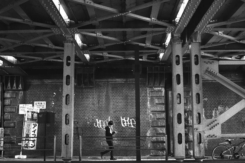 Man walking dim railway underpass