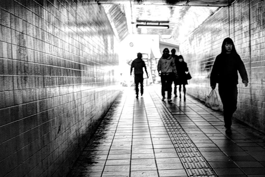 薄暗い通路を歩く人びと