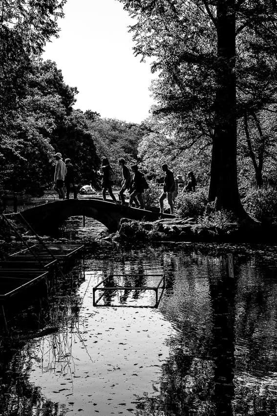 Silhouettes on small stone bridge