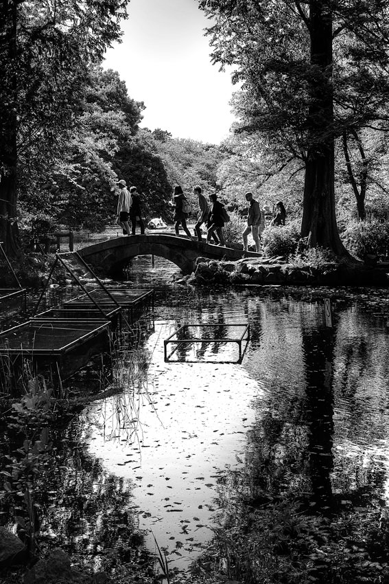 Silhouettes on small stone bridge