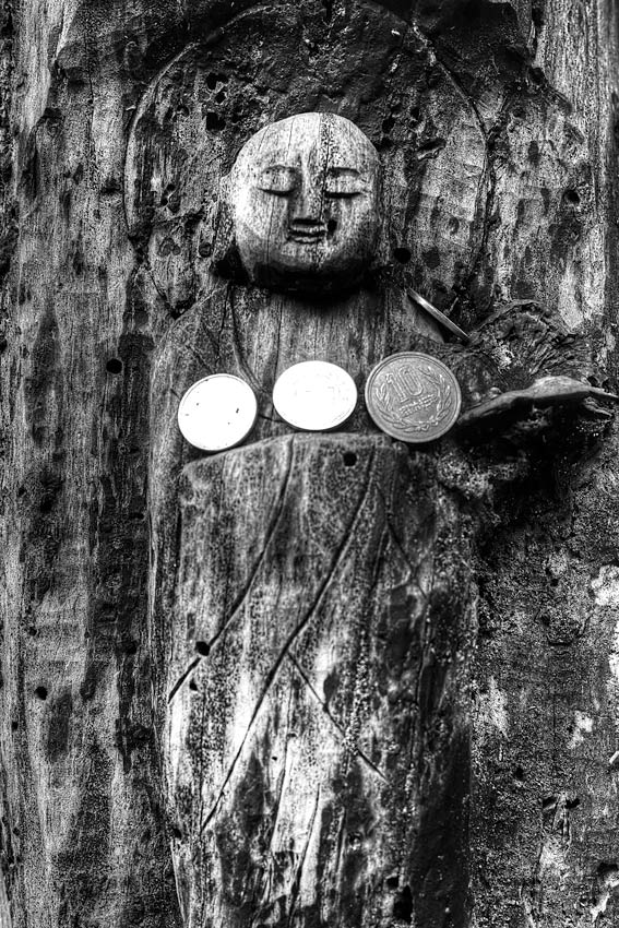 wooden Buddha statue and coins