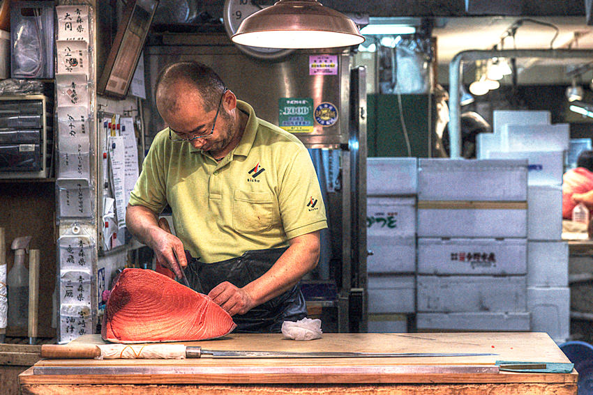 Man cutting tuna block