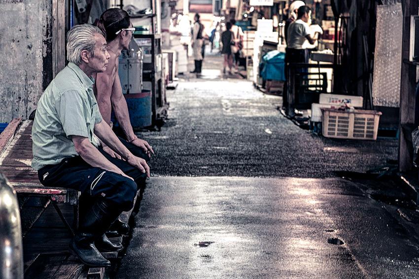 通路に腰掛ける二人の男