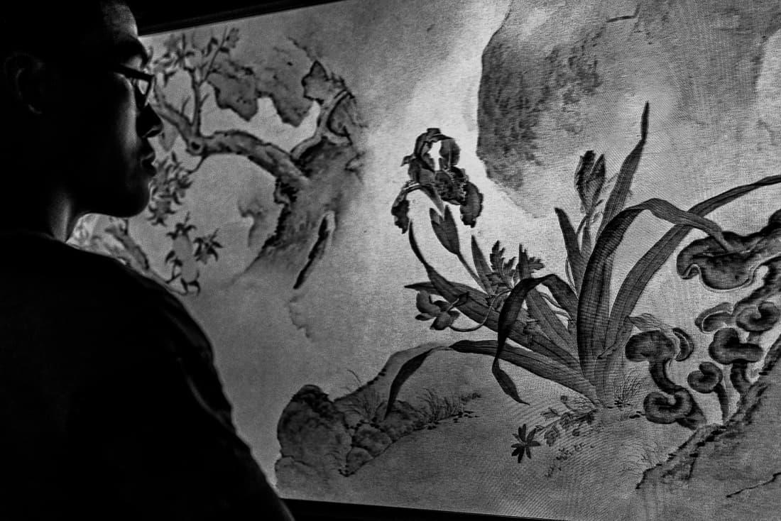 スクリーンに表示された水墨画を眺める男