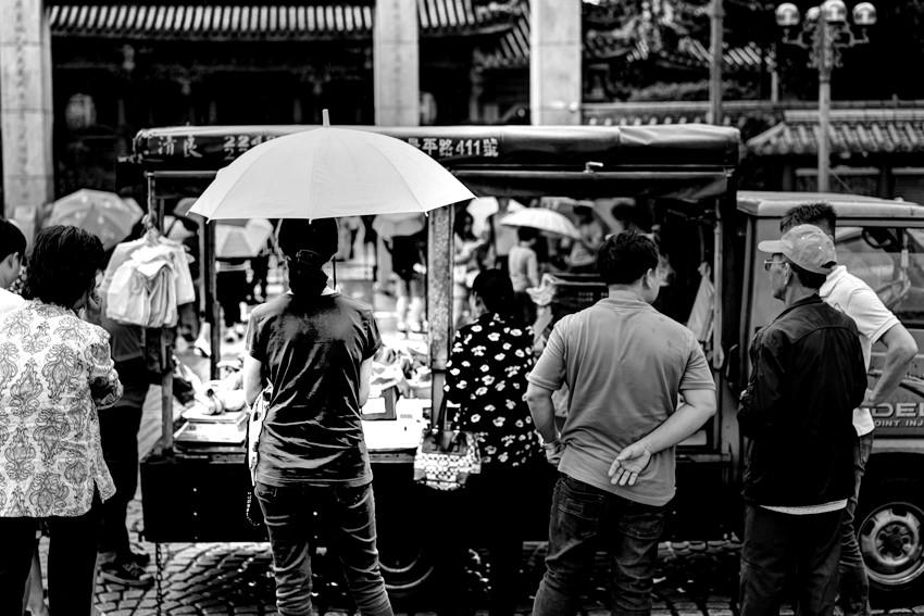 傘を差す若い女性の後ろ姿